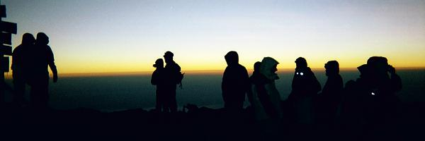 Silhouettes of the group at the summit sign (left of picture), with headlights still on at sunrise