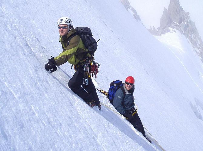 Climbing a steep snow slope, with the belayer using a bucket seat belay.
