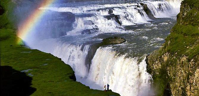 Two trekkers silhouetted against the double waterfall of Gulfoss
